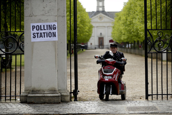 A Chelsea Pensioner drives his mobility scooter past a sign for a polling station after voting in London, Thursday, May 6, 2021. Millions of people across Britain will cast a ballot on Thursday, in local elections, the biggest set of votes since the 2019 general election. A Westminster special-election is also taking place in Hartlepool, England. (AP Photo/Matt Dunham)