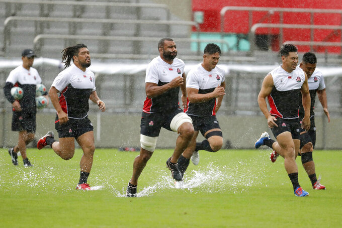Japan's rugby team players practice ahead of their match against Scotland as Typhoon Hagibis approaches Saturday, Oct. 12, 2019. Tokyo and surrounding areas braced for a powerful typhoon forecast as the worst in six decades, with streets and trains stations unusually quiet Saturday as rain poured over the city. (Yuki Sato/Kyodo News via AP)