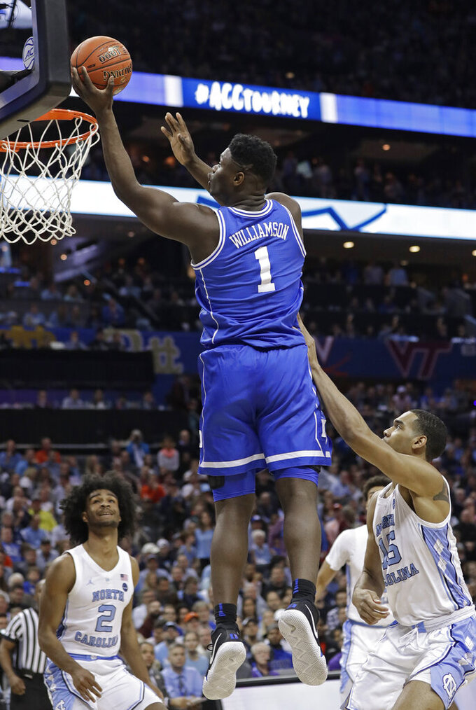 Duke's Zion Williamson (1) shoots against North Carolina's Coby White (2) and Garrison Brooks (15) during the first half of an NCAA college basketball game in the Atlantic Coast Conference tournament in Charlotte, N.C., Friday, March 15, 2019. (AP Photo/Chuck Burton)