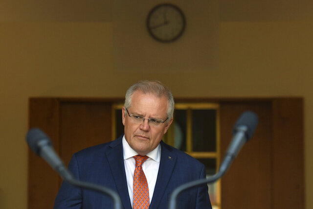 Australian Prime Minister Scott Morrison arrives to give an update on the coronavirus at a press conference at Parliament House in Canberra, Wednesday, Jan. 29, 2020. Australia and New Zealand will work together to evacuate their isolated and vulnerable citizens from China's virus-hit Hubei province. (Mick Tsikas/AAP Image via AP)