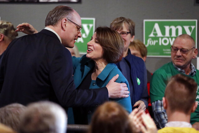 FILE - In this Feb. 1, 2020 file photo Democratic presidential candidate Sen. Amy Klobuchar, D-Minn., center, gets a kiss from husband John Bessler, upon arriving at a rally in Sioux City, Iowa. Sen. Klobuchar announced Monday, March 23 that her husband has tested positive for the coronavirus.(AP Photo/Gene J. Puskar File)