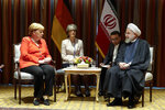 In this photo released by the official website of the office of the Iranian Presidency, President Hassan Rouhani, right, meets Germany's Chancellor Angela Merkel, left, on the sideline of the United Nations General Assembly at the United Nations Headquarters Tuesday, Sept. 24, 2019. (Iranian Presidency Office via AP)