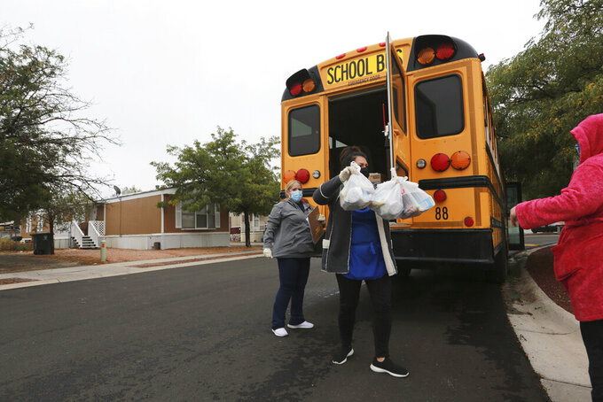 FILE - In this Sept. 9, 2020, file photo, Santa Fe Public School food workers Dolores Rodella and Eva Dominguez distribute lunches and breakfasts at a bus stop during the coronavirus pandemic in Santa Fe, New Mexico. New Mexico ranked 49th in a report released Monday, June 21, 2021, measuring child wellbeing based on data gathered before the pandemic. That's an improvement over last year when the state ranked 50th among U.S. states. (AP Photo/Cedar Attanasio, File)