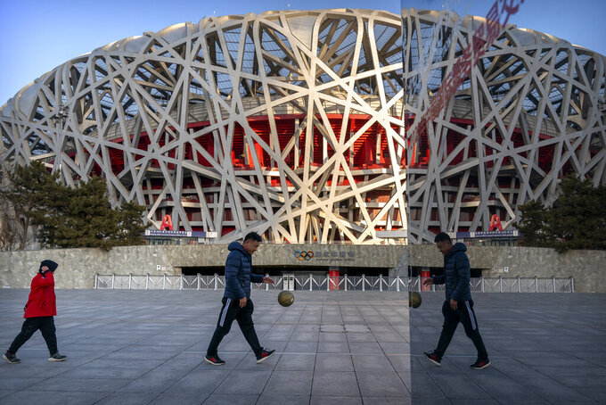 """A man and a boy walk past the National Stadium, also known as the Bird's Nest, which will again be a venue for the 2022 Beijing Winter Olympics, in Beijing, Tuesday, Feb. 2, 2021. The 2022 Beijing Winter Olympics will open a year from now. Most of the venues have been completed as the Chinese capital becomes the first city to hold both the Winter and Summer Olympics. Beijing held the 2008 Summer Olympics. But these Olympics are presenting some major problems. They are already scarred by accusations of rights abuses including """"genocide""""against more than 1 million Uighurs and other Muslim ethnic groups in western China. (AP Photo/Mark Schiefelbein)"""