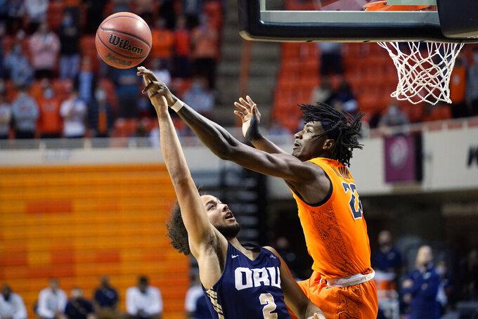 Oklahoma State forward Kalib Boone (22) blocks a shot by Oral Roberts guard Kareem Thompson (2) during the first half of an NCAA college basketball game Tuesday, Dec. 8, 2020, in Stillwater, Okla. (AP Photo/Sue Ogrocki)