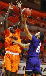 TCU's Alex Robinson (25) shoots as Oklahoma State's Yor Anei (14) defends in the second half of a NCAA college basketball game in Stillwater, Okla., Monday, Feb. 18, 2019. (Nate Billings/The Oklahoman via AP)