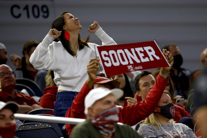 A fan dances as another holds up an Oklahoma banner during the first half of the Cotton Bowl NCAA college football game between Oklahoma and Florida in Arlington, Texas, Wednesday, Dec. 30, 2020. (AP Photo/Ron Jenkins)