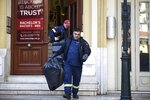 A firefighter leaves a college, holding a plastic bag after employees received suspicious envelopes in the northern port city of Thessaloniki, Greece, Friday, Jan. 11, 2019. At least nine people have received medical attention after about a dozen letters containing a white powder described as consisting of