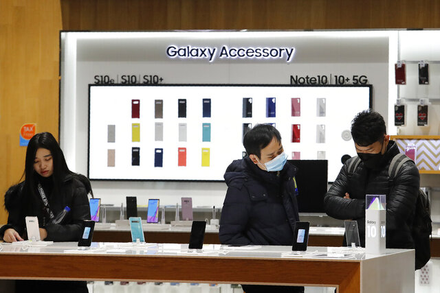 Visitors watch Samsung Electronics' Galaxy 10 smartphones at its shop in Seoul, South Korea, Thursday, Jan. 30, 2020. Samsung Electronics Co. said Thursday its operating profit for the last quarter fell 33.7% from a year earlier but it predicted earnings will improve in 2020, driven by a gradually stabilizing computer chip market and increasing 5G smartphone sales. (AP Photo/Ahn Young-joon)