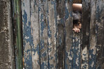 A boy peaks from the dilapidated doorway of his home as his mother receives soap and detergent distributed by volunteers as an effort to avoid the spread of the new coronavirus, in the Rocinha slum of Rio de Janeiro, Brazil, Tuesday, March 24, 2020. (AP Photo/Leo Correa)