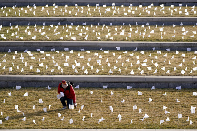 A man places flags at the National World War I Museum and Memorial Tuesday, Jan. 19, 2021, in Kansas City, Mo. The 1,665 flags represent the area residents who died in the coronavirus pandemic and the display was part of a national memorial to lives lost to COVID-19. (AP Photo/Charlie Riedel)