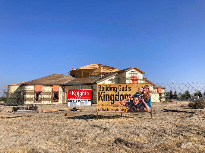 """A sign reads """"Building God's Kingdom"""" at the St. Charles Borromeo Catholic Church construction site in Visalia, Calif., on Thursday, Aug. 26, 2021. It's billed as the largest Catholic parish in the United States and it's being constructed about 200 miles north of Los Angeles, in what's often referred to """"as the heart of California's dairy industry."""" (Alejandra Molina/RNS via AP)"""