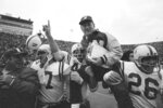 FILE - In this Nov. 25, 1971, file photo, Nebraska head coach Bob Devaney is carried off the field by his victorious players after Nebraska defeated Oklahoma 35-31 in an NCAA college football game in Norman, Okla. Reports that Nebraska wants to back out of playing at Oklahoma this season didn't sit well with one of the stars of the 1971 Game of the Century. The game scheduled Sept. 18 in Norman, Oklahoma, would mark the 50th anniversary of Nebraska's 35-31 win over the Sooners in a clash of the Nos. 1 and 2 teams in the nation. (AP Photo/File)