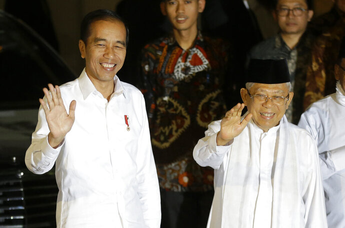 Incumbent Indonesian President Joko Widodo, left, and his running mate Ma'ruf Amin wave to reporters, in Jakarta, Indonesia, Thursday, June 27, 2019. Indonesia's top court has rejected a challenge to election results that alleged massive and systematic fraud, paving the way for Joko Widodo's second term as president. (AP Photo/Achmad Ibrahim)