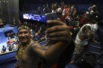 An indigenous man poses for a selfie during a meeting with lawmakers to discuss land rights and the Chamber of Deputies' role in the protection of the environment in Brasilia, Brazil, Thursday, April 25, 2019.  Discussions held in congressional chambers Thursday were occurring on the sidelines of an annual three-day protest known as the Free Land Encampment in Brasilia. (AP Photo/Eraldo Peres)