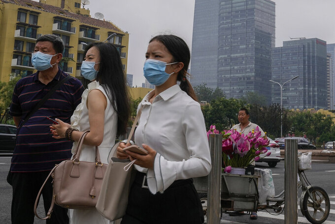 People wearing face masks to help curb the spread of the coronavirus stand watch near a vendor selling flowers outside a subway station in Beijing, Thursday, July 22, 2021. A senior Chinese health official says China cannot accept the World Health Organization's plan for the second phase of a study into the origins of COVID-19. (AP Photo/Andy Wong)