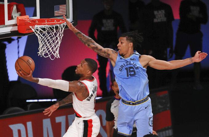 Portland Trail Blazers Damian Lillard (0) shoots the ball against Memphis Grizzlies Brandon Clarke (15) during the second half of an NBA basketball game Friday, July 31, 2020, in Lake Buena Vista, Fla. (Mike Ehrmann/Pool Photo via AP)