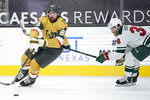 Vegas Golden Knights right wing Alex Tuch (89) skates around Minnesota Wild right wing Ryan Hartman (38) during the second period of an NHL hockey game Saturday, April 3, 2021, in Las Vegas. (AP Photo/John Locher)