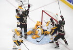 Nashville Predators goalie Juuse Saros (74) looks up from the ice as Arizona Coyotes' Brad Richardson (15) and teammate Michael Grabner (40) celebrate a goal during overtime in an NHL hockey playoff game Friday, Aug. 7, 2020, in Edmonton, Alberta. (Jason Franson/Canadian Press via AP)