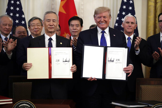 FILE - In this Jan. 15, 2020, file photo President Donald Trump holds a trade agreement with Chinese Vice Premier Liu He, in the East Room of the White House in Washington. Trump spent four years upending seven decades of American trade policy. He started a trade war with China, slammed America's closest allies by taxing their steel and aluminum and terrified Big Business by threatening to take a wrecking ball to $1.4 trillion in annual trade with Mexico and Canada.  Trump's legacy on trade is likely to linger, regardless whether Joe Biden replaces him in the White House in January 2021.(AP Photo/Evan Vucci)