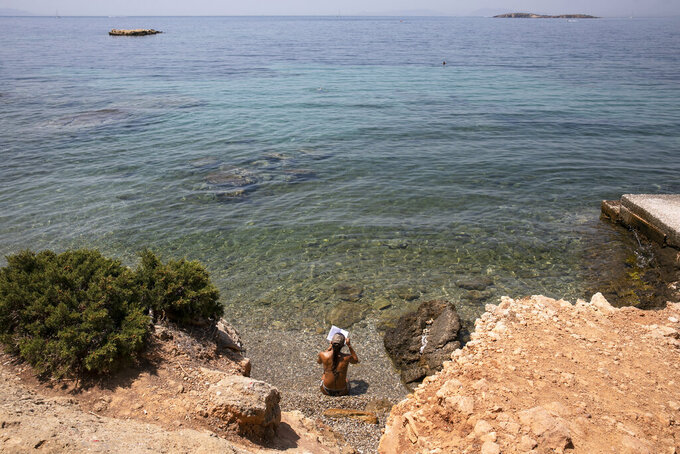 A woman reads a book at a beach of Kavouri suburb, southwest of Athens, on Friday, July 30, 2021. Greek authorities ordered additional fire patrols and infrastructure maintenance inspections Friday as the country grappled with a heat wave expected to last more than a week, with temperatures expected to reach 42 C (107.6 F). (AP Photo/Yorgos Karahalis)
