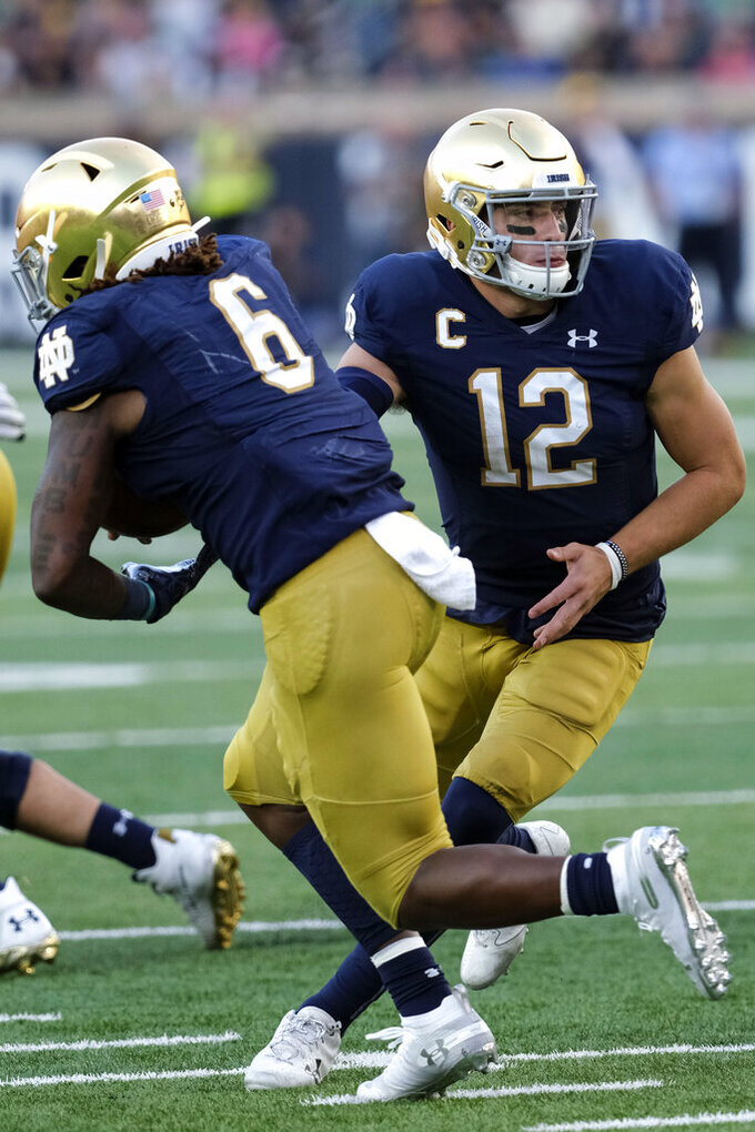 Notre Dame quarterback Ian Book (12) hands off to teammate Tony Jones Jr. (6) in the second half of an NCAA college football game in South Bend, Ind., Saturday, Sept. 28, 2019. Notre Dame won 35-20. (AP Photo/AJ Mast)