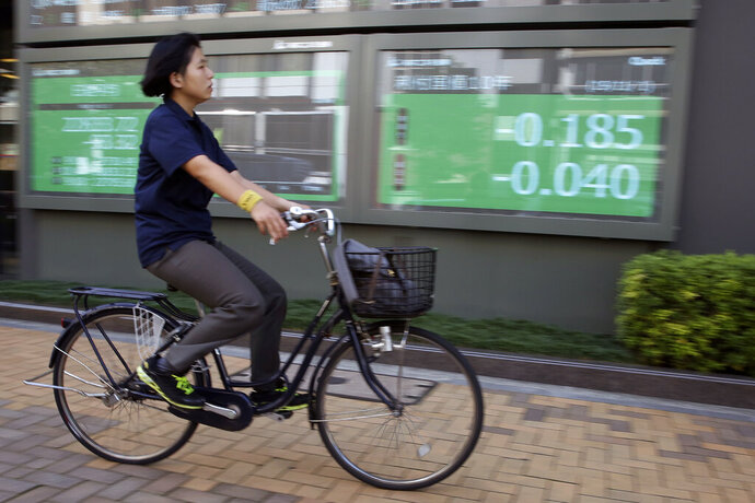 A woman cycle pasts in front of an electronic stock board of a securities firm in Tokyo, Friday, Nov. 1, 2019. Asian shares were mixed on Friday after investors were spooked by a report that cast doubt on the prospects of a long-term U.S-China trade deal.(AP Photo/Koji Sasahara)
