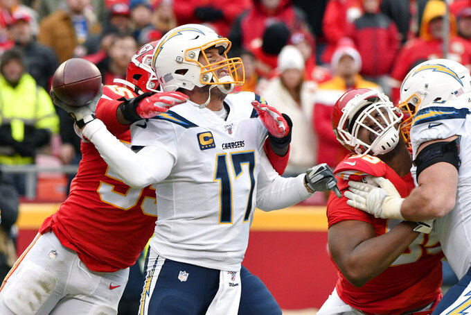 Los Angeles Chargers quarterback Philip Rivers (17) throws under pressure from Kansas City Chiefs defensive end Frank Clark (55) during the second half of an NFL football game in Kansas City, Mo., Sunday, Dec. 29, 2019. (AP Photo/Ed Zurga)