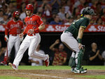 Los Angeles Angels' Taylor Ward, left, scores without a throw to Oakland Athletics catcher Sean Murphy on a single by David Fletcher during the fifth inning of a baseball game in Anaheim, Calif., Tuesday, Sept. 24, 2019. (AP Photo/Alex Gallardo)