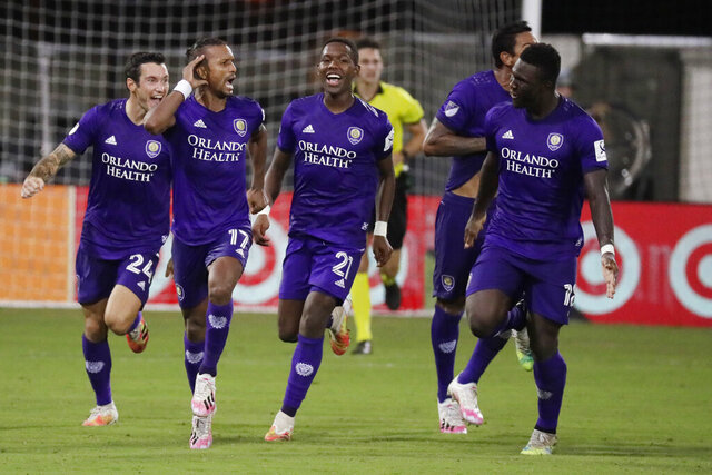 Orlando City forward Nani (17) celebrates after scoring the winning goal with teammates Kyle Smith (24), Andres Perea (21), Antonio Carlos (25) and Daryl Dike (18) after an MLS soccer match against Los Angeles FC, Friday, July 31, 2020, in Orlando, Fla. (AP Photo/John Raoux)