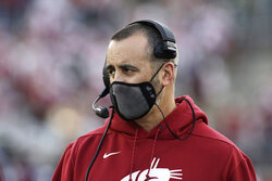 FILE - In this Saturday, Oct. 16, 2021, file photo, Washington State coach Nick Rolovich watches during the first half of an NCAA college football game against Stanford in Pullman, Wash. The NHL suspending San Jose's Evander Kane 21 games for submitting a fake vaccination card and Washington State firing football coach Nick Rolovich for failing to comply with a vaccine mandate Monday provided two more reminders of the impact the coronavirus is still having on professional and college sports. (AP Photo/Young Kwak, File)
