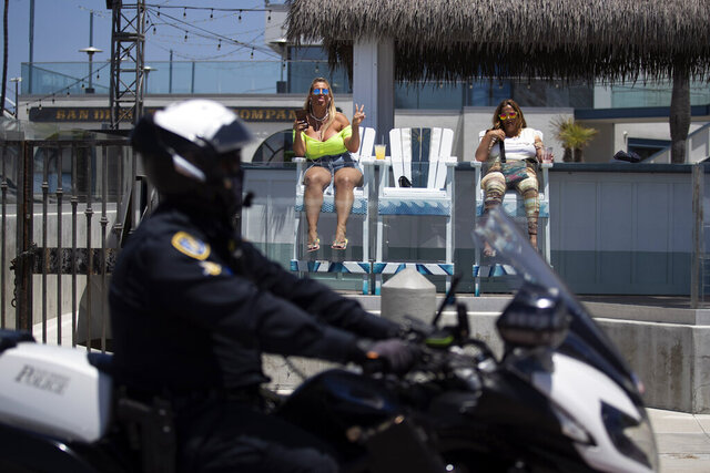 A San Diego police official passes on motorcycle as two women drink at an beachfront restaurant Friday, May 22, 2020, in San Diego. Millions of Californians are heading into the Memorial Day weekend with both excitement and anxiety after restrictions to control the spread of coronavirus were eased across much of the state. (AP Photo/Gregory Bull)