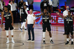 From left, Milwaukee Bucks' Giannis Antetokounmpo (34), head coach Mike Budenholzer, Khris Middleton (22), and Eric Bledsoe (6) react during the second half of an NBA conference semifinal playoff basketball game against the Miami Heat, Wednesday, Sept. 2, 2020, in Lake Buena Vista, Fla. The Heat won 116-114. (AP Photo/Mark J. Terrill)