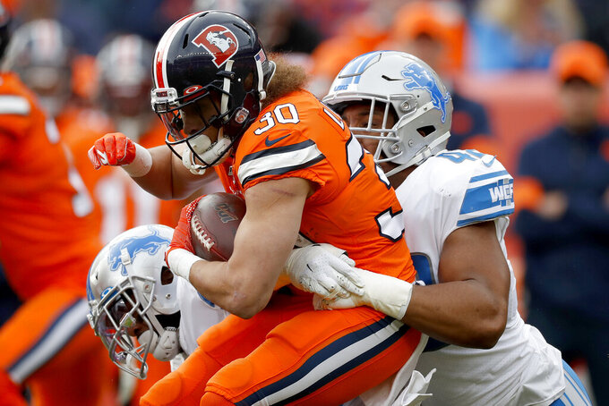 Denver Broncos running back Phillip Lindsay (30) is tackled by Detroit Lions outside linebacker Devon Kennard during the first half of an NFL football game, Sunday, Dec. 22, 2019, in Denver. (AP Photo/David Zalubowski)