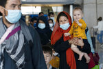 Families evacuated from Kabul, Afghanistan, walk through the terminal before boarding a bus after they arrived at Washington Dulles International Airport, in Chantilly, Va., on Tuesday, Aug. 24, 2021. (AP Photo/Jose Luis Magana)