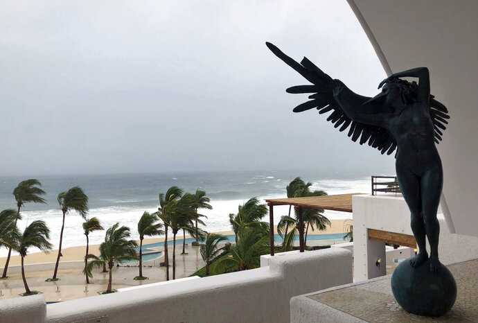Palm trees bend in heavy winds along the ocean coast as seen from the Marquis Los Cabos Resort, in San Jose del Cabo, Mexico, Thursday, June 14, 2018. Tropical Storm Bud continued to weaken as it neared the southern end of the Baja California peninsula and its popular resorts on Thursday. (AP Photo/Juliet Williams)