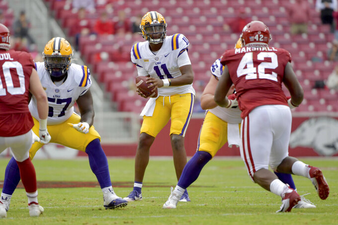 LSU quarterback TJ Finley (11) drops back to pass against Arkansas during the first half of an NCAA college football game Saturday, Nov. 21, 2020, in Fayetteville, Ark. (AP Photo/Michael Woods)