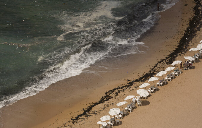 In this Aug. 8, 2019, photo, garbage creeps towards the shore at Stanley Beach in Alexandria, Egypt. Authorities say that 11 people drowned off the coast of northern Egypt on Friday, July 10, 2020 at a beach known for its rocky jetty and fast-moving waters. (AP Photo/Maya Alleruzzo, file)