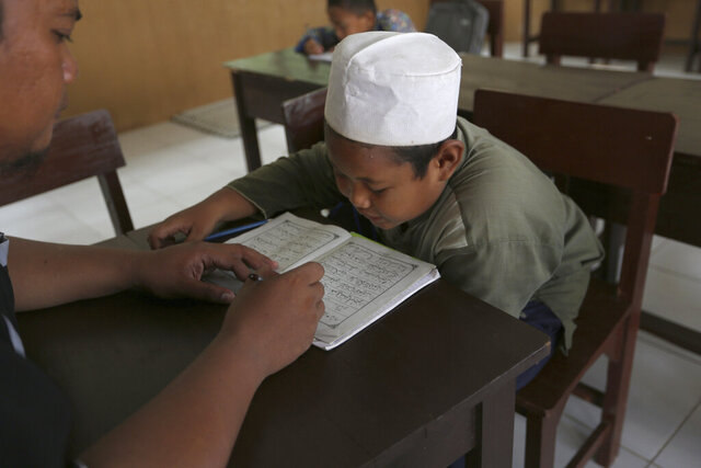 A Muslim student reads the Quran at an Islamic boarding school in Tenggulun, East Java, Indonesia, on Saturday, April 27, 2019. The school is part of Ali Fauzi's Circle of Peace Foundation, which Fauzi created in a bid to combat violent extremism. (AP Photo/Tatan Syuflana)