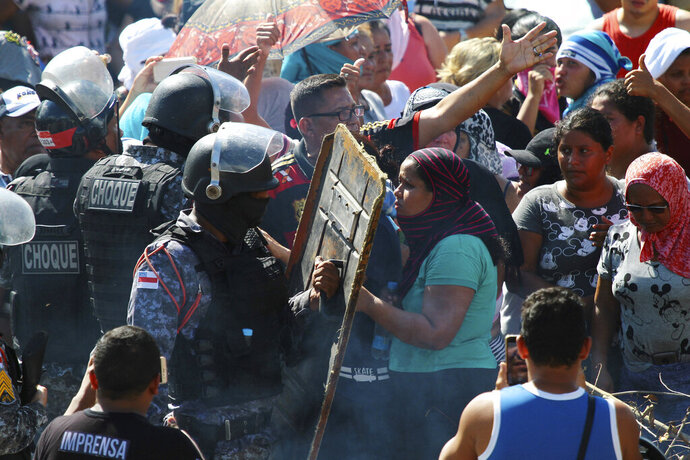 Relatives argue with police for more information outside the Anisio Jobim Prison Complex where a deadly riot erupted among inmates in Manaus in the northern state of Amazonas, Brazil, Sunday, May 26, 2019. A statement from the state prison secretary says prisoners began fighting among themselves around noon Sunday, and security reinforcements were rushed to complex. (AP Photo/Edmar Barros)