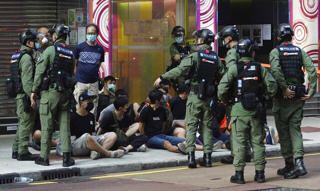 People, sitting on the ground, are arrested by police officers at a downtown street in Hong Kong Sunday, Sept. 6, 2020. About 30 people were arrested Sunday at protests against the government's decision to postpone elections for Hong Kong's legislature, police and a news report said. (AP Photo/Vincent Yu)