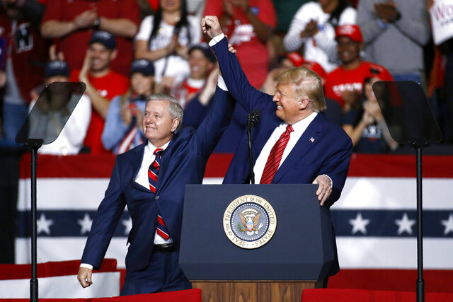 FILE - In this Feb. 28, 2020 file photo, Sen. Lindsey Graham, R-S.C., left, stands onstage with President Donald Trump during a campaign rally,  in North Charleston, S.C. The filing period for South Carolina's 2020 primaries and November general election closed Monday, March 30 although the coronavirus outbreak has left in flux how exactly the elections will be carried out. Perhaps the most highly anticipated election contest coming up in South Carolina is Graham's pursuit of a fourth term in office. A general election matchup with Democrat Jaime Harrison all but certain, Graham has also drawn a handful of Republican challengers, as well as Constitution and Libertarian party opponents.   (AP Photo/Patrick Semansky, File)