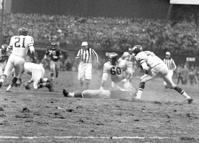 FILE - In this Nov. 21, 1960, file photo, New York Giants' Frank Gifford lies on field as play continues after he was knocked unconscious by Philadelphia Eagles' Chuck Bednarik (60) as Gifford was carrying the ball in the fourth quarter of a football game at New York's Yankee Stadium. The NFL revealed 70 of the 100 greatest plays in league history on Friday night with a TV special produced by NFL Films that has everything from spectacular offensive performances to defensive gems. In balloting conducted by The Associated Press, 68 media members on a nationwide panel voted for their top 100. Among those disclosed is the brutal hit applied by Bednarik on Gifford in 1960. (AP Photo/File)