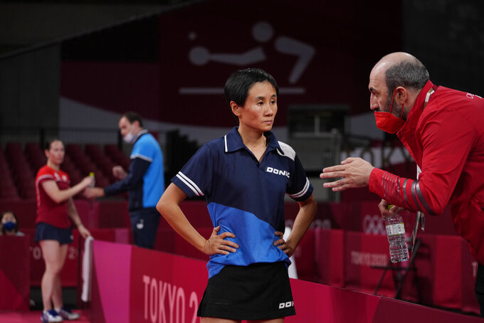 Austria's Liu Jia listens to her coach during the table tennis women's singles second round match against Russia's Polina Mikhailova at the 2020 Summer Olympics, Monday, July 26, 2021, in Tokyo. (AP Photo/Kin Cheung)