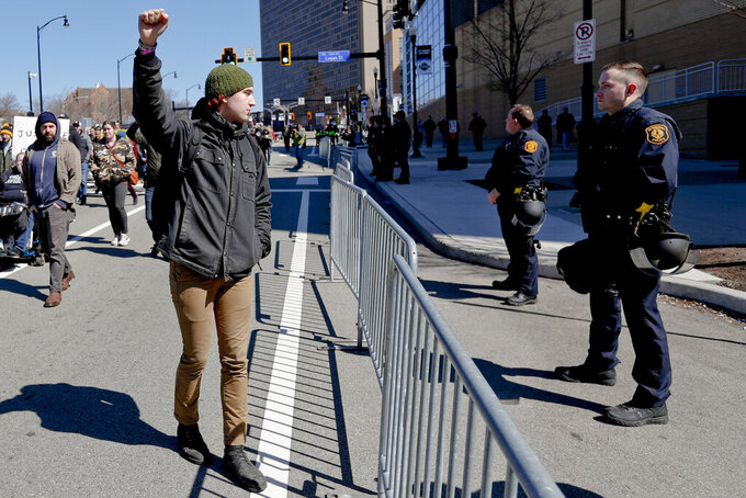 "FILE -In this March 23, 2019 file photo, a marcher holds up his fist while staring at police lined up in front of PPG Paints Arena in Pittsburgh during a protest after a former suburban police officer was acquitted of a homicide charge in the on-duty shooting death of Antwon Rose II in East Pittsburgh. In a private Facebook group called the Pittsburgh Area Police Breakroom, many current and retired officers spent the year criticizing chiefs that took a knee or officers who marched with Black Lives Matter protesters, who they called ""terrorists"" or ""thugs.""   (AP Photo/Keith Srakocic)"