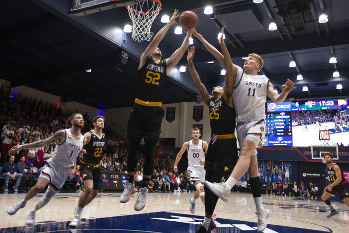 Winthrop guard Chandler Vaudrin (52) and Saint Mary's forward Matthias Tass (11) vie for a rebound over Winthrop forward Josh Ferguson (25) during the first half of an NCAA college basketball game, Monday, Nov. 11, 2019 in Moraga, Calif. (AP Photo/D. Ross Cameron)