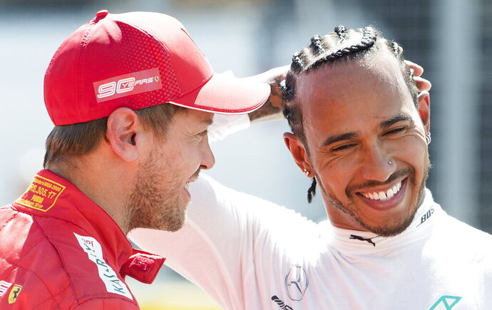 Ferrari driver Sebastian Vettel of Germany, left, talks with Mercedes driver Lewis Hamilton of Great Britain after winning pole position during qualifying for the Formula One Canadian Grand Prix auto race in Montreal, Saturday, June 8, 2019.  (Graham Hughes/The Canadian Press via AP)