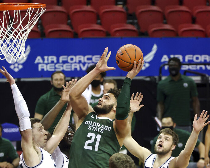 Colorado State guard David Roddy (21) shoots as Utah State forward Justin Bean, left, and Utah State guard Rollie Worster, right, during the second half of an NCAA college basketball game in the semifinal round of the Mountain West Conference men's tournament Friday, March 12, 2021, in Las Vegas. (AP Photo/Isaac Brekken)