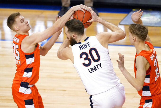 Virginia forward Jay Huff (30) battles for a rebound with Syracuse guard Buddy Boeheim (35) and Syracuse forward Marek Dolezaj (21) during the second half of an NCAA college basketball game in the quarterfinal round of the Atlantic Coast Conference tournament in Greensboro, N.C., Thursday, March 11, 2021. (AP Photo/Gerry Broome)