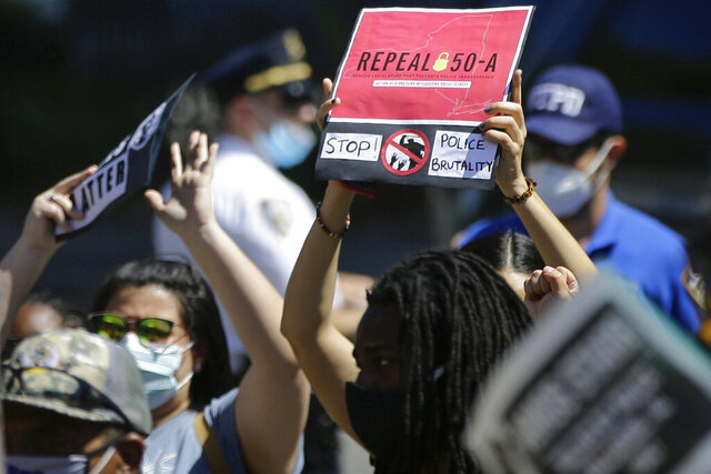 FILE- In this June 8, 2020 file photo, a protester holds a sign outside Queens County Criminal Court calling for the repeal of section 50-a, a law prohibiting the public release of police officer disciplinary records. On Thursday, Sept. 17, 2020, a federal appeals court agreed to keep the release of New York City police disciplinary records on pause while public safety unions fight a lower-court decision that had cleared the way for their disclosure. (AP Photo/Frank Franklin II, File)